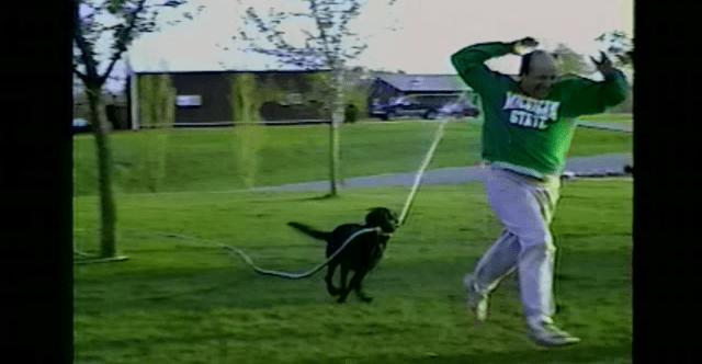 水が出ているホースをくわえたワンコに追いかけられる飼い主、びしょ濡れだけど嬉しそう!